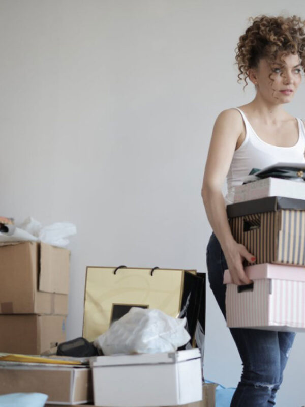 stressed woman moving house carrying cardboard house